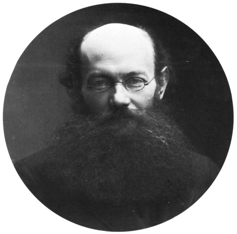 Black adn white photo of balding man with long black beard and small wire-rimmed glasses.